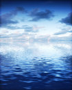 Ocean with calm waves background with dramatic sky blue cold tint Stock Images