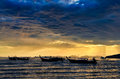 Ocean coast cloudy colorful sunset and fishing boats Royalty Free Stock Photos
