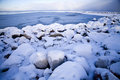 Ocean freezing to ice during cold winter gn snow covered stones with that in the background Stock Photography