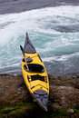 Ocean kayak beached on rocky shore at tidal rapids Royalty Free Stock Photography