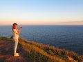 Seaside hill with young woman at sunset Royalty Free Stock Photo