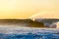 Ocean large wave dawn surfer photo image of distant unidentified unrecognizable going over the with spray surging pushing white Royalty Free Stock Photography