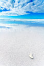 Ocean seascape white rock pebble white sandy beach under blue cloudy sky bad weather waves background Stock Photos