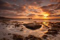 Ocean sunset tide pool at low tide with scripps pier in background Royalty Free Stock Photos