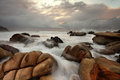 Ocean surges over weathered rocks the well at forresters beach nsw australia Stock Images