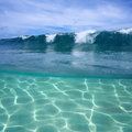 Ocean wave breaking and underwater sandy seabed split view of sunlight on Stock Images