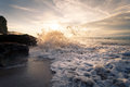 Ocean wave with foam beating against the rocks at sunset Royalty Free Stock Photo