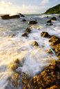 Ocean waves against rocks on the beach at sunset Royalty Free Stock Photos