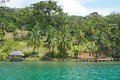 Oceanfront caribbean property in central america with coconut palm trees and a house with hut over water panama bocas del toro Royalty Free Stock Image