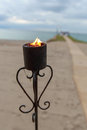 Oceanfront wedding torch at sunset with lit torches focus is on Royalty Free Stock Photos