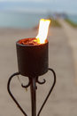 Oceanfront wedding torch at sunset with lit torches focus is on Royalty Free Stock Image