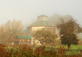 Octagon barn on a foggy autumn morning Stock Images