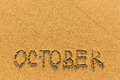 October - word inscription on the gold sand beach. Royalty Free Stock Photo