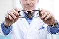 Oculist at work giving a pair of glasses during a visit Royalty Free Stock Photography