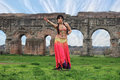 Odalisque belly dancer with ancient roman aqueducts ruins in the background Stock Photo