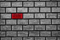 Odd one standing out red color brick in an all gray wall Royalty Free Stock Image