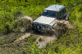 Off-road vehicle brand Nissan Patrol overcomes a pit of mud Royalty Free Stock Photo