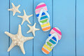 Off to the beach starfish sea shells and rainbow coloured flip flops over wooden blue background Stock Image