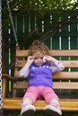 stock image of  Offended little girl sitting on a bench with cookies