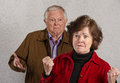 Offended senior woman mature wife near frustrated husband with hands up Royalty Free Stock Photo