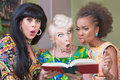Offended trio of women three mature reading a hardcover book Royalty Free Stock Photos