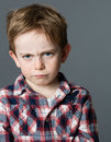 Offended young child sulking and pouting expressing kid anger Royalty Free Stock Photo