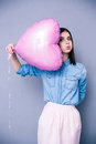 Offended young girl holding heart shaped balloon over gray background looking at camera Royalty Free Stock Images