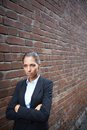 Offense image of angry businesswoman walking along brick wall Stock Images