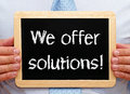 We offer solutions written on blackboard held by businessman Royalty Free Stock Images