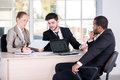 Office affairs three successful business people sitting in the and do while businessmen communicate with each Royalty Free Stock Image
