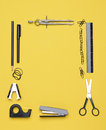 Office back to school supplies and on a yellow background looking down on the all black and chrome tools from an overhead angle Royalty Free Stock Photography
