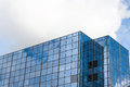 Office building with glass surface reflecting blue cloudy sky Royalty Free Stock Photo
