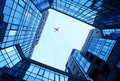 Office buildings as a frame and sky with blue airplane Stock Photography
