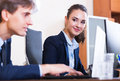 Office colleagues successfully working together young indoors and smiling Stock Photos