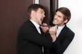 Office conflict two angry young business men fighting at Stock Photos