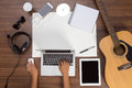 Office desk background hand using a laptop acoustic guitar and headphones Royalty Free Stock Photo