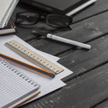 Office desk with business objects - open notebook, tablet computer, glasses, ruler, pencil, pen. Free space for text. Royalty Free Stock Photo