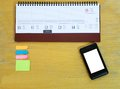 Office desk wood with day planner smartphone and sticky notes Royalty Free Stock Images