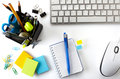 Office desktop with keyboard mouse notebook and basket of writing tools Stock Photo
