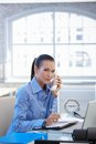 Office girl taking landline call worker writing notes looking at camera smiling Stock Photography