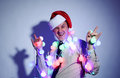 Office man in a Santa Claus red cap with colored garlands Royalty Free Stock Photo