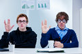 Office nerds gesturing prosperity salute two male workers with a nerdy appearance gesture the made popular by a well known Royalty Free Stock Photo