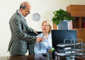 Office scene with two elderly and happy workers Royalty Free Stock Photo