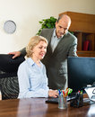 Office scene with two mature and smiling workers Royalty Free Stock Photo