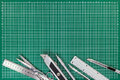 Office supplies on cutting mat - cutters, scissors, mechanical p Royalty Free Stock Photo