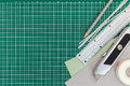 Office supplies over green cutting mat background. top view. Royalty Free Stock Photo