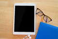 Office table with Blank tablet screen and blue notepad paper. Royalty Free Stock Photo