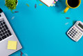 Office table desk with set of colorful supplies, white blank note pad, cup, pen, pc, crumpled paper, flower on blue Royalty Free Stock Photo