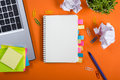 Office table desk with set of colorful supplies, white blank note pad, cup, pen, pc, crumpled paper, flower on orange Royalty Free Stock Photo