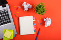 Office table desk with set of colorful supplies, white blank note pad, cup, pen, pc, crumpled paper, flower on red Royalty Free Stock Photo